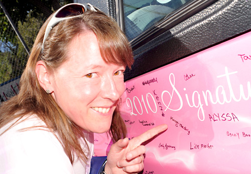 Karen Grigoleit of TRU's Institutional Planning and Analysis indicates where she wrote her name on a pink Tracker called Wheels of Hope. Wheels shared the booth with Pinking.