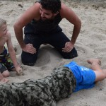 An instructor kneels beside children on the beach showing them how help an unconscious person rescued from the water.