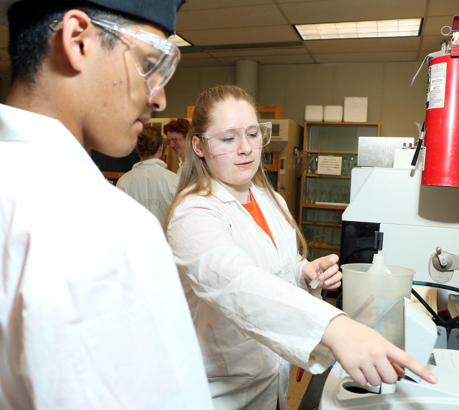 Lacey Banman, a fourth-year Bachelor of Science student majoring in chemistry and math, helps a visiting student.