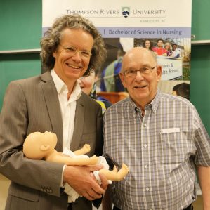 President Alan Shaver with Ken Lepin and baby Florence at the School of Nursing's live birthing demo.