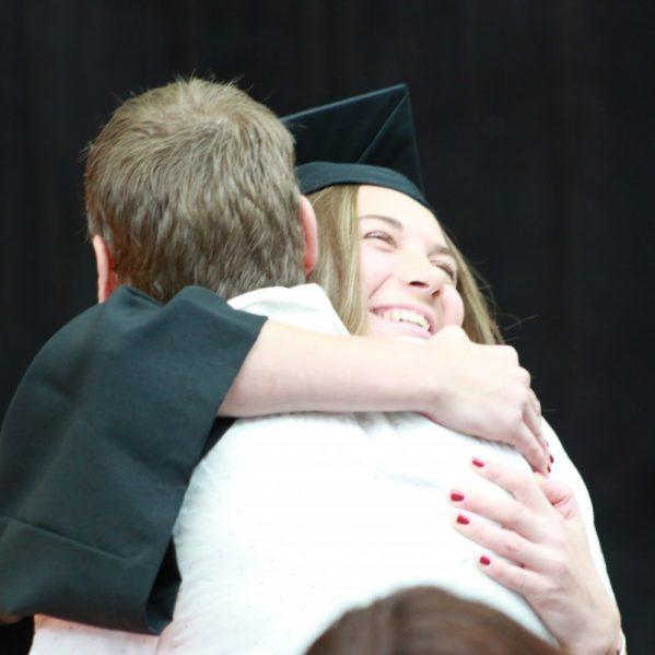Grad hugs family member