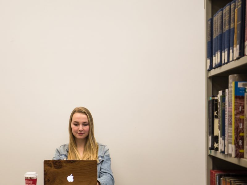 A student reads an open textbook on a laptop.