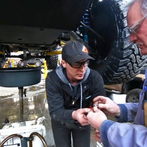 Faculty member and students performing oil change
