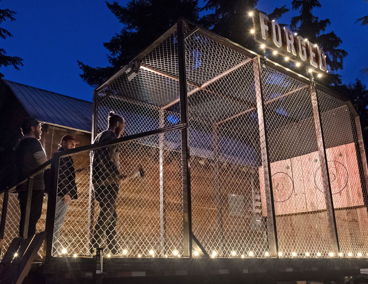Forged Axe Throwing mobile cage lit at night