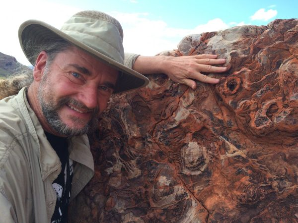 Dr. Bruce Damer stands next to a 3.6-billion-year-old artifact representing buried layers of molecular structures, thought to be the framework for the origin of life.