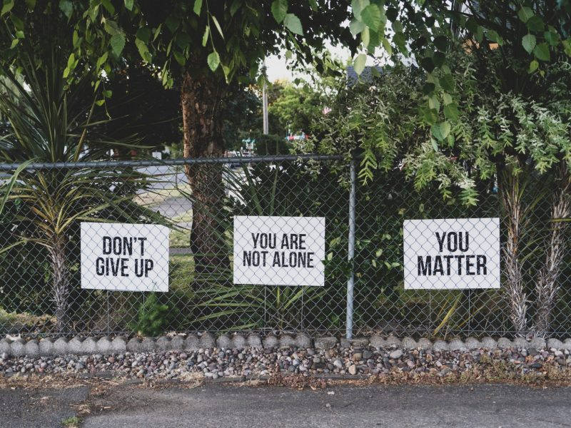 signs on a chainlink fence that say Don't Give up, You are not alone and You Matter