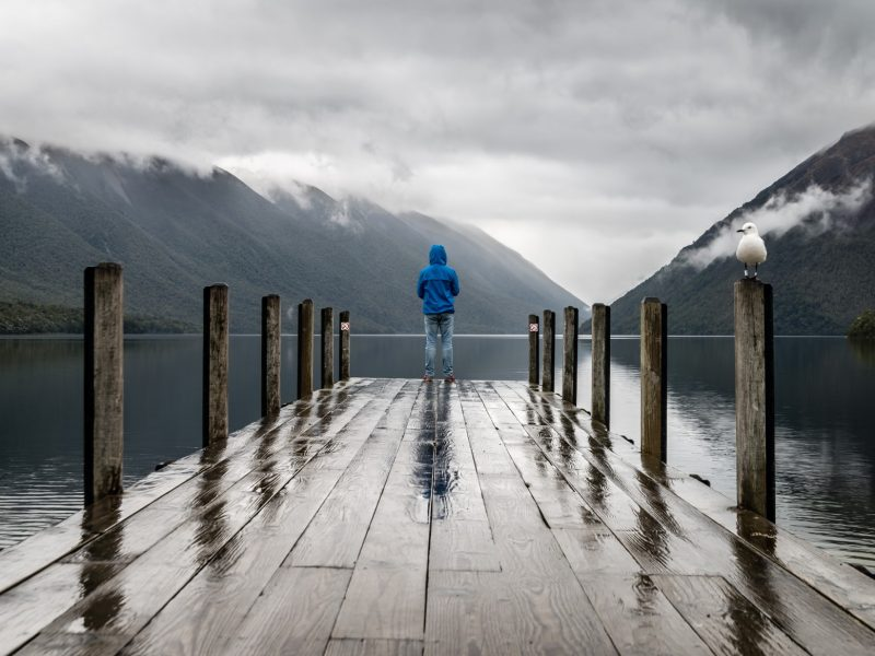 person standing on the edge of a dock on a cloudy day