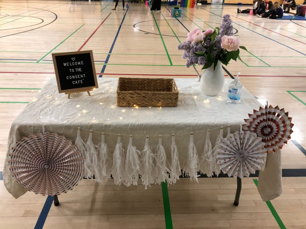 """Table covered in a white cloth, decorations, a """"Welcome to the Consent Café"""" sign, and a vase with pink flowers."""